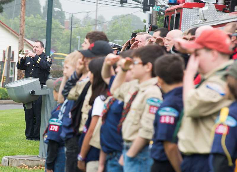 by: NEWS-TIMES PHOTO - Boy scouts look on at the bugler on Memorial Day.