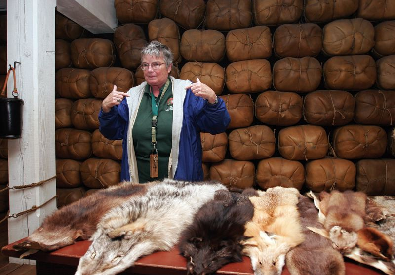 by: JIM CLARK/PAMPLIN MEDIA GROUP - (ABOVE) Fort Vancouver volunteer Betty Meeks shows visitors a collection of animal pelts that are stored in a replica of the fort's trading post.