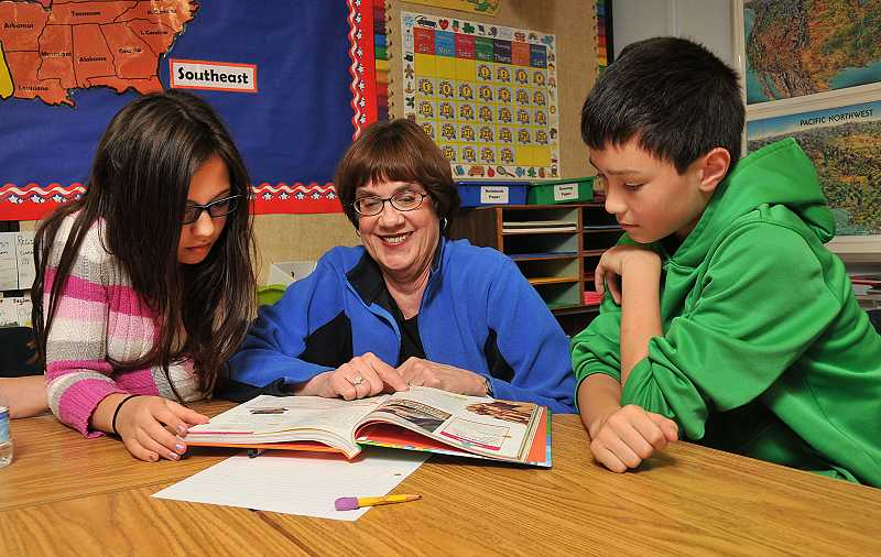 by: REVIEW PHOTO: VERN UYETAKE - Marjorie Reay helps Eliza Buchanan and Ben Burk with their school work