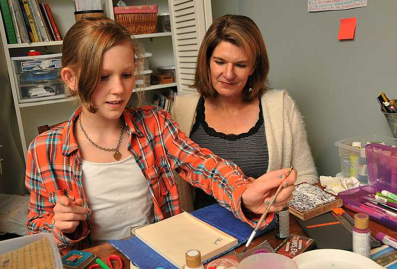 by: REVIEW PHOTO: VERN UYETAKE - Janet Creasy, right, with her daughter, Tess, works on an art project.