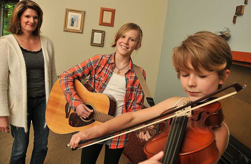 by: REVIEW PHOTO: VERN UYETAKE - Janet Creasy, left, observes her daughters, Tess, left, and Ava, exploring their musical passion during a typical homeschool session.