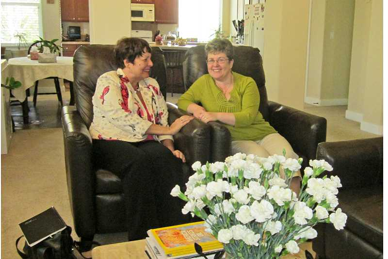 by: BARBARA SHERMAN - ALL THE COMFORTS OF HOME - Nancy Raske (left), owner of NW Senior Resources Inc., vists with Alina Stoica, owner of Golden Years Adult Care Home on Bull Mountain, who has room for four senior residents.