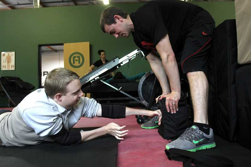 by: TIMES PHOTO: JONATHAN HOUSE - With the help of Scott Fuller, a trainer at ADAPT in Beaverton, Jake French practices punching a soft bag to work on his upper body strength.
