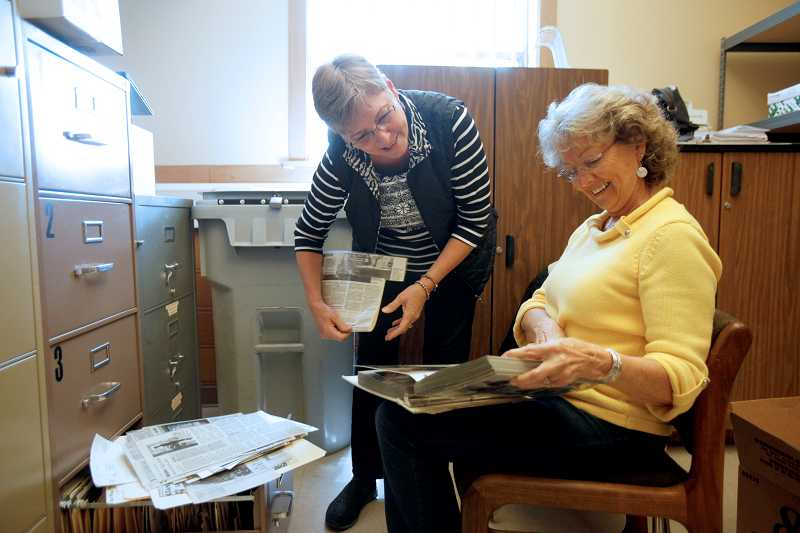 by: TIMES PHOTO: JONATHAN HOUSE - Judy Chown, left, and Mary Boger, go through old articles and photos in the Arts and Communication Magnet Academy's archives as they search for material to put on the memory board for the school's upcoming 20th anniversary celebration on Sunday.
