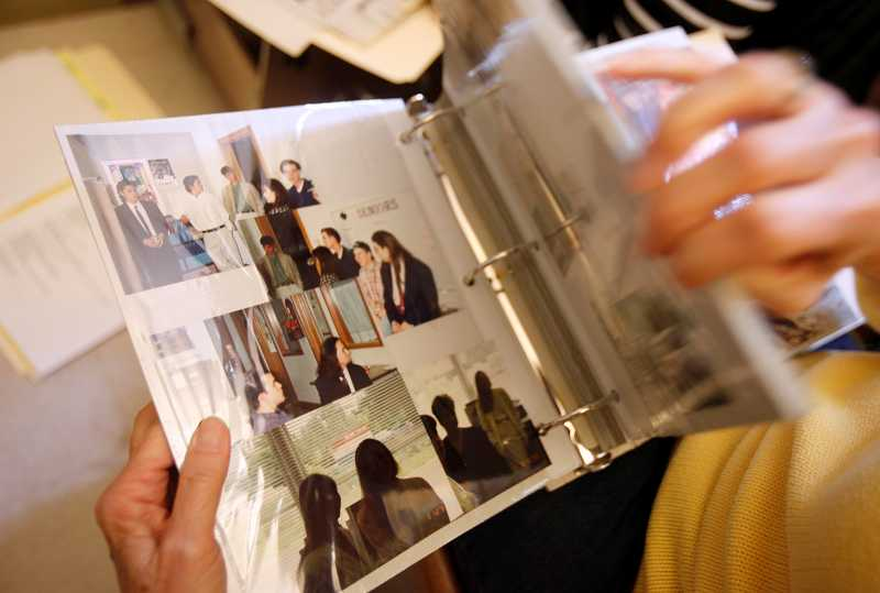 by: TIMES PHOTO: JONATHAN HOUSE - Mary Boger looks through an old album of ACMA photographs taken in the early 1990s, soon after the school's founding.