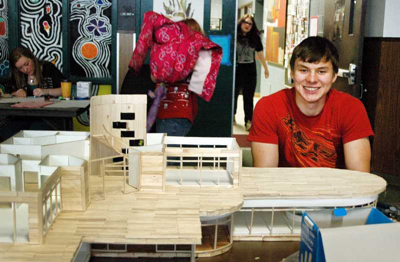 by: ISABEL GAUTSCHI - Best In Show senior Caleb Boeck sits before his scale model of a luxury house.