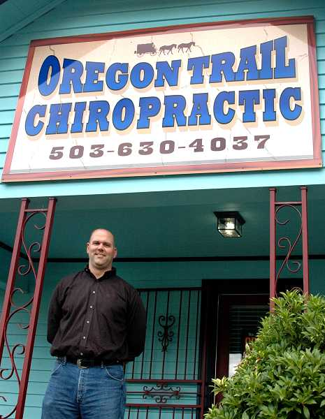 by: ISABEL GAUTSCHI - Jonathan Rhue stands before the Oregon Trail Chiropractic Clinic. He cant wait to paint the building off-white.