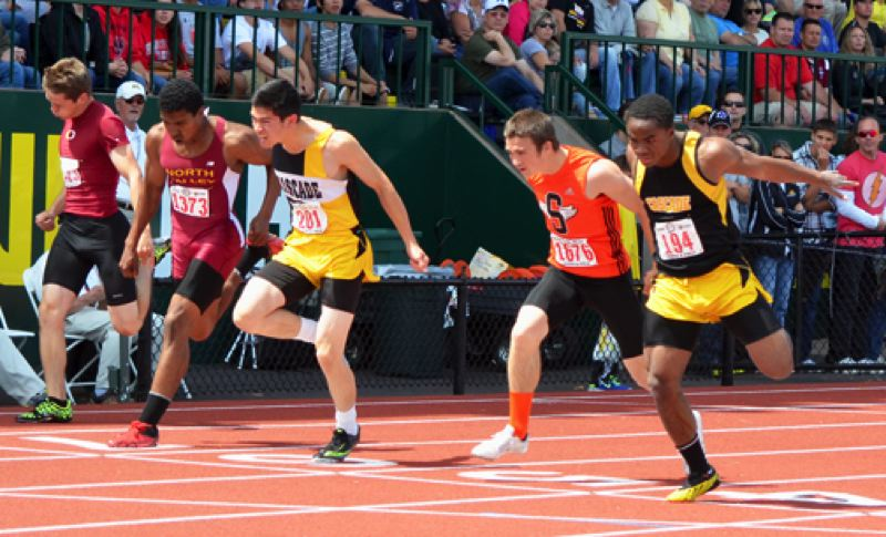 by: JOHN BREWINGTON - Scappoose's Paul Revis (in orange) was a close fourth in the 100 meter dash.