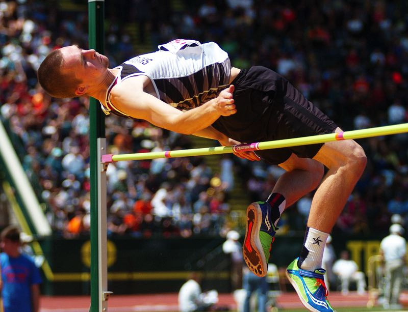 by: DAN BROOD - UP AND OVER -- Sherwood High School senior Zach Milligan clears the bar during the high jump event at the state meet. Milligan, and his younger brother, Ben, placed second and third, respectively.