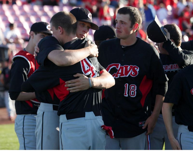 by: PHOTO BY JONATHAN HOUSE - There was plenty of emotion near Clackamas dugout following Saturdays state final with Sheldon. Above senior Jared Bell (4) receives a hug from classmate Skylar Schlunz, while senior Jarrod Switzer (18) waits to give a supportive hug.