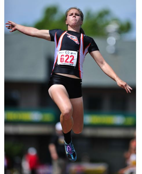 by: BY JOHN LARIVIERE - Madison Cronin flies in the state finals of the triple jump at the University of Oregons Hayward Field. The Gladstone High School senior won the event with a career-best mark of 35-10-3/4.