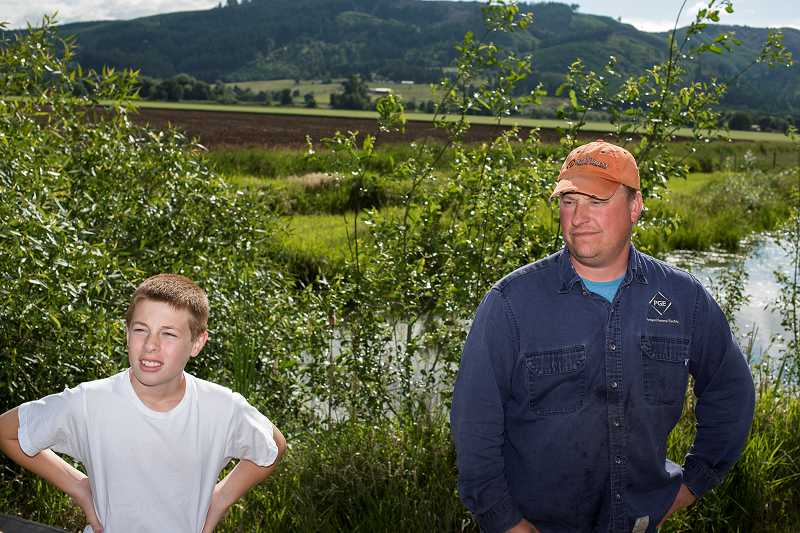 by: NEWS-TIMES PHOTOS: CHASE ALLGOOD - Double Pond shimmers behind James Chrisman (right), whose stress levels go down when he throws a bobber into the calm waters -- until David Trent calls the police on him and his stress levels skyrocket. Chrisman is glad he finally got a chance to hear Trents side of the pond story, although he still thinks Trent should use discretion and not call the police on him and his neighbor, Alec Lecarno (left).