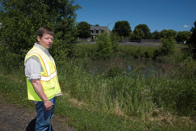 by: NEWS-TIMES PHOTOS: CHASE ALLGOOD - Doug Meeker of Forest Groves public works department stands near one of the citys four publicly maintained year-round ponds that double as water quality facilities. Unlike Double Pond, this one -- at Willamina and Strasburg -- is fenced because of the steep, brushy sides that people might easily stumble down and into the water.