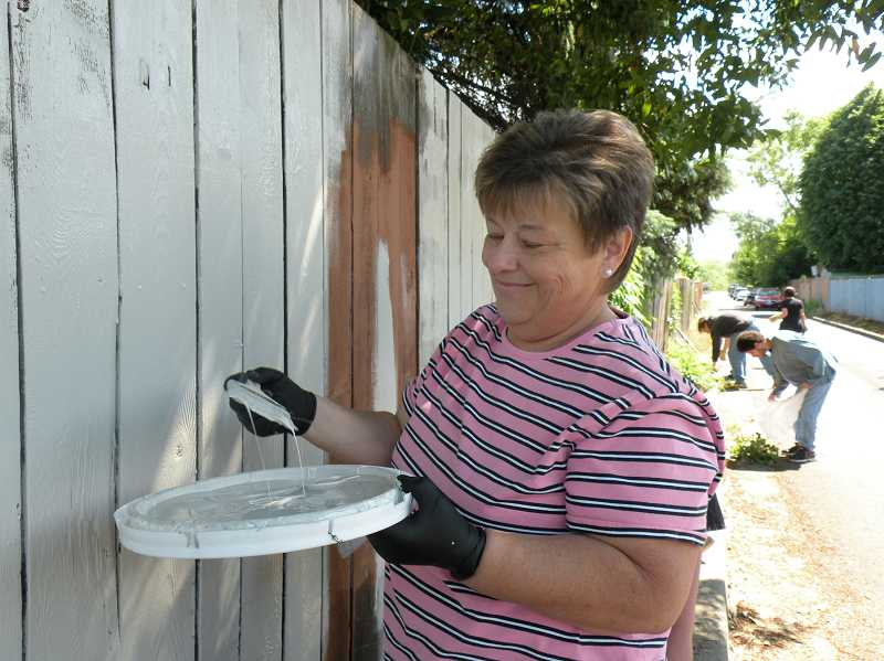 by: COURTESY PHOTO: CALLIE VOGEL - Instead of sitting in a pew, listening to a sermon, Debbie Keuhn helped paint over graffiti one recent Sunday morning at a problematic private-property site in Cornelius.