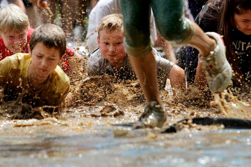 by: TIMES PHOTO: JONATHAN HOUSE - Students slide through mud during the Falcon Dash, held Friday at Fowler Middle School. The obstacle course is a yearly fundraiser for the schools Parent Student Organization and helps pay for items the school wouldnt be able to afford otherwise.