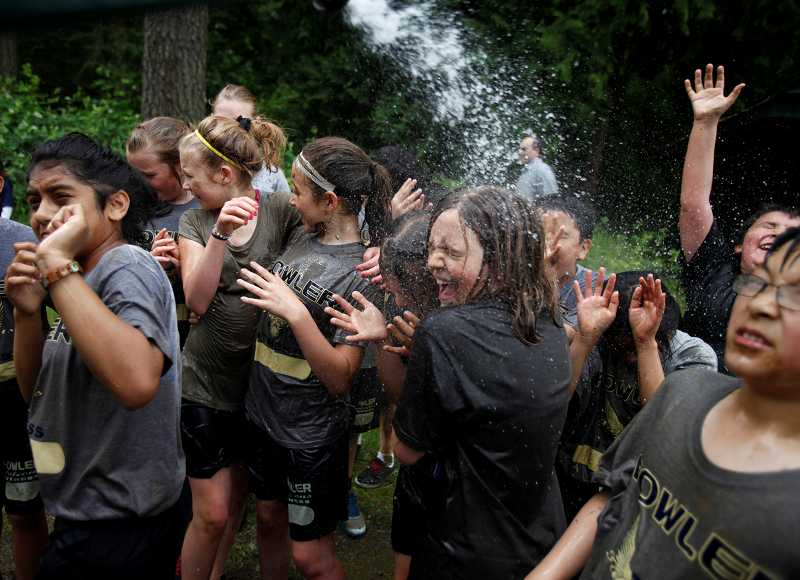 by: TIMES PHOTO: JONATHAN HOUSE - Students wash off the mud and grass stains after completing the Falcon Dash at Fowler Middle School.
