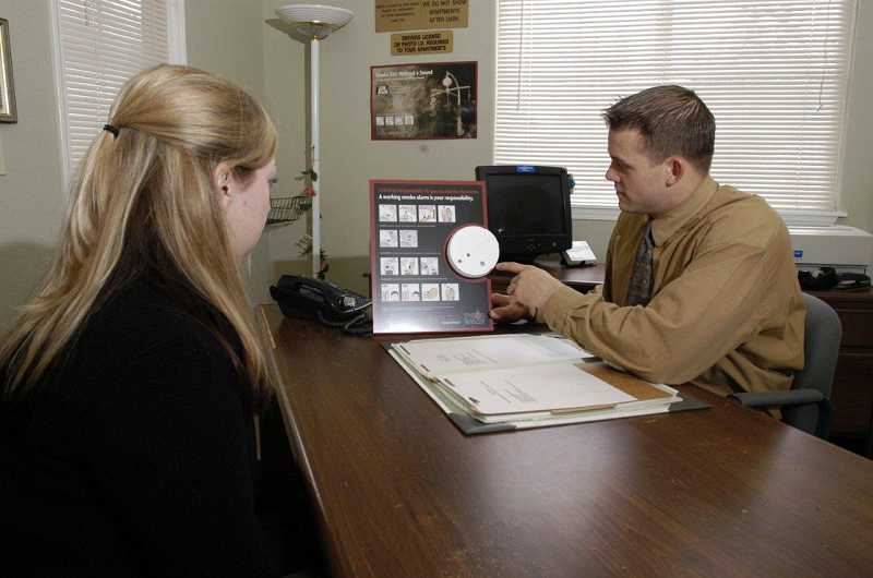 by: SUBMITTED PHOTO: TVF&R - A landlord shows a tenant a smoke alarm using one of the TVF&R display boards.
