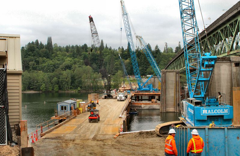 by: DAVID F. ASHTON - This massive east-side work, extending halfway into the Willamette River, is on the temporary construction bridge which holds tons of heavy construction equipment.