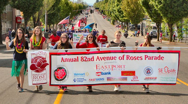 by: DAVID F. ASHTON - Volunteers carry the banner that signals the start of the 7th Annual 82nd Avenue of Roses Parade.