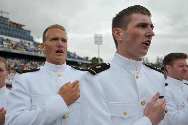 by: SUBMITTED PHOTO: U.S. NAVAL ACADEMY - Robert Bruss, left, and Brendan Hanlon sing the U.S. Naval Academy school song during their May 24 commencement ceremony.