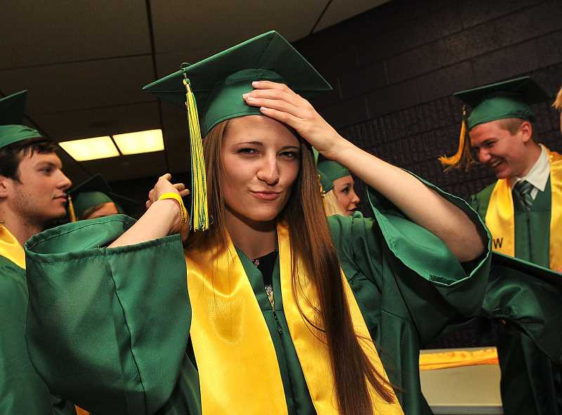 by: TIDINGS PHOTOS: VERN UYETAKE - Emma Jones fixes her cap prior to the ceremony.