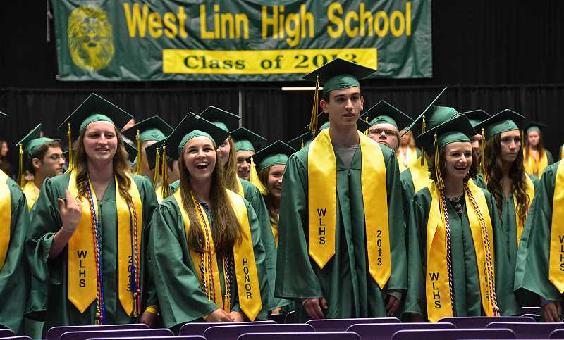 by: VERN UYETAKE - Graduates watch as their classmates enter the Chiles Center.