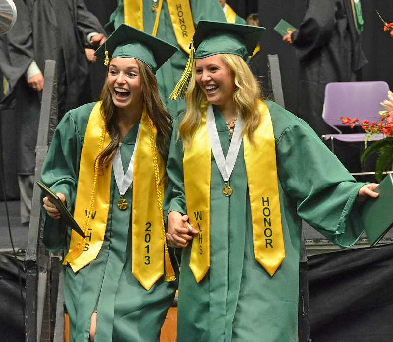 by: VERN UYETAKE - Briana Barzola and Paige Myers exit the stage with their diplomas.