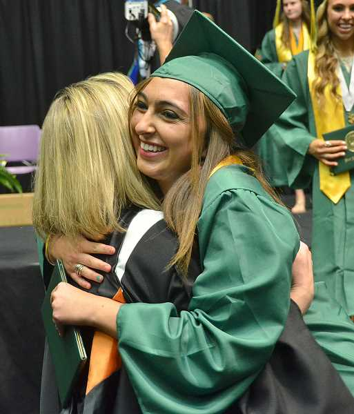 by: VERN UYETAKE - Madison Baldwin hugs Marlo McKennon after receiving her diploma.