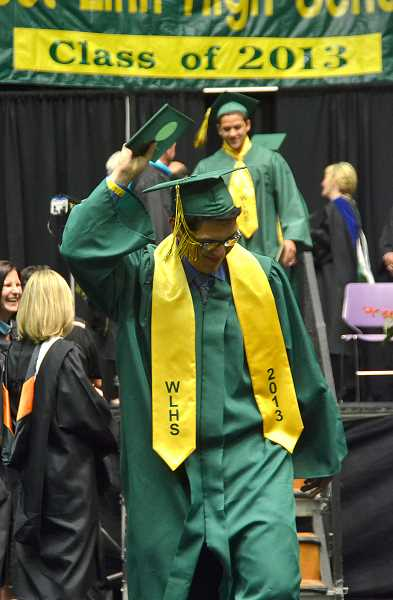 by: VERN UYETAKE - Tyler Chay leaves the stage with his diploma.