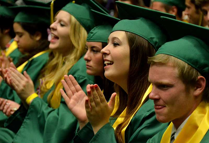 by: VERN UYETAKE - Graduates cheer on their fellow classmates.