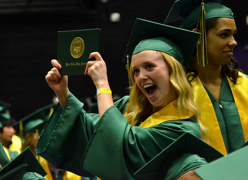 by: VERN UYETAKE - Leah Merriam shows off her diploma.