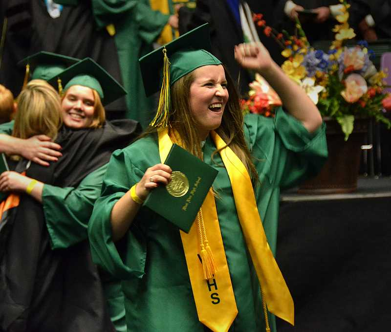 by: VERN UYETAKE - Emmalee Scheid celebrates after receiving her diploma.