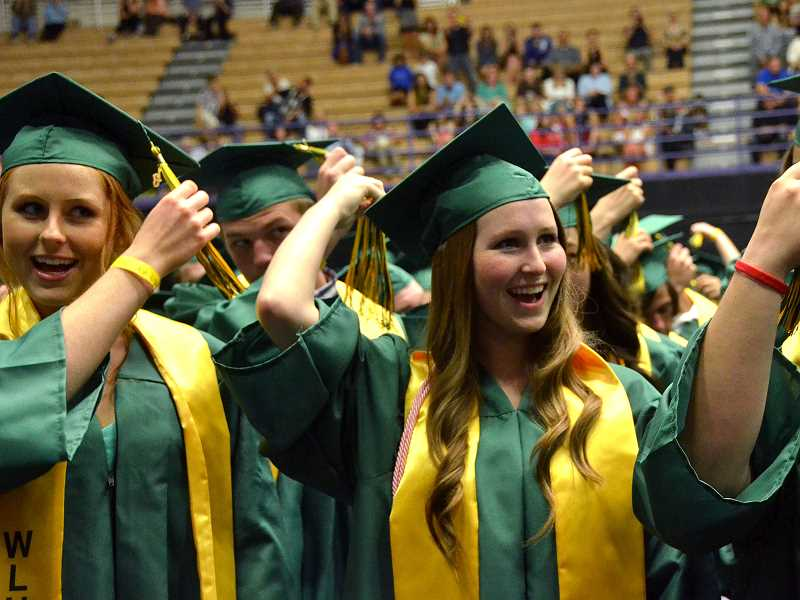 by: VERN UYETAKE - Jessi Kindley, left, and Allie Kirsch turn their tassels.