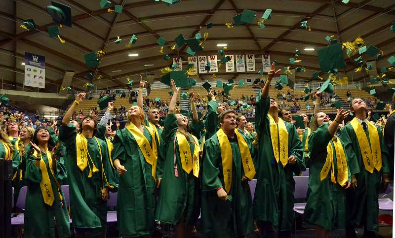 by: VERN UYETAKE - Graduates let their caps fly at the end of the ceremony.