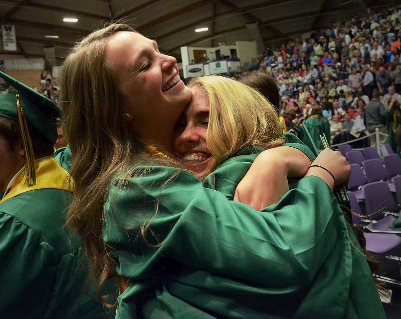 by: VERN UYETAKE - Taylor Backa, left, and Sophie Bangs embrace at the end of the commencement.