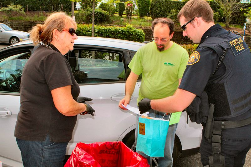 by: DAVID F. ASHTON - Portland Office of Neighborhood Involvement (ONI) Crime Prevention Coordinator Katherine Anderson tells a man calling himself only Jack about the drug turn-in program, while an officer checks his bag, to make sure it contains no needles or glass.