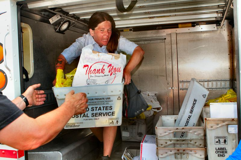 by: DAVID F. ASHTON - Returning from her postal route south of S.E. Powell Boulevard, USPS Letter Carrier Aimee Anderson hands off food she collected at the Sellwood Postal Station at S.E. Ochoco at 17th.