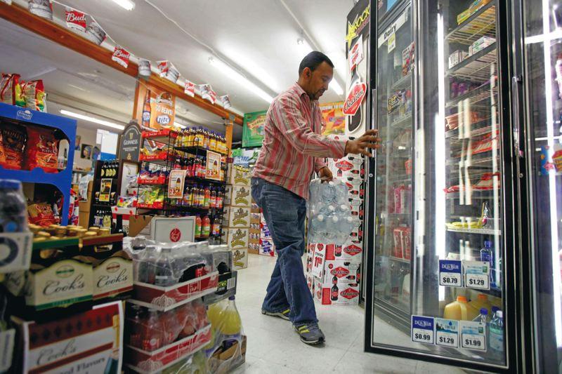 by: TRIBUNE PHOTO: JONATHAN HOUSE - There are still more convenience store items than groceries in Asfaw Chaneyalews Triple Crown Market, but Chaneyalew is trying to change that, with the help of his Kenton neighbors.