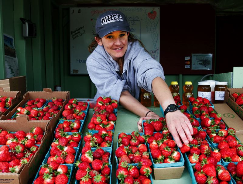 by: OUTLOOK PHOTO: JIM CLARK - Mandy Olsen of Fuji Farms fruit stand in Troutdale, tidies up the strawberry display.