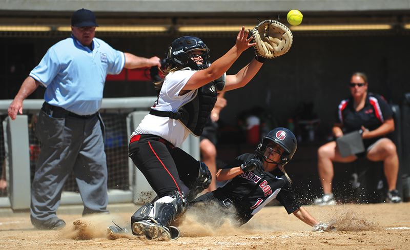 by: HILLSBORO TRIBUNE PHOTO: ZACK PALMER - Glencoe freshman Macy Besuyen slides underneath the tag of North Medford catcher Katie Williamson for Glencoe's only run.