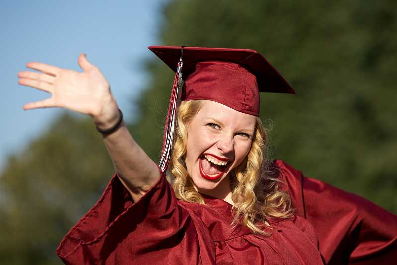by: JAIME VALDEZ - Elizabeth Walker waves to her friend, Mitchell Schwabel, as she processes with her senior class to Aaron J. Contreras Memorial Stadium for Sherwood High School's commencement.