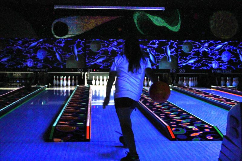 by: OUTLOOK PHOTO: ANNE ENDICOTT - Cosmic Bowling at PinbusterZ Family Fun Center features shorter lanes and lighter weight bowling balls for the preteen crowd, in a black light setting.