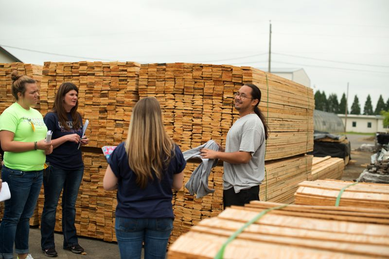 by: PHOTO COURTESY OF PATTY SALAZAR - Clackamas students talk to Titus (far right) about his duties in the woodshop where he works with other MacLaren Youth Correctional Facility residents. The residents get paid to make pallets for local business and other wood products they make are sent to the Army.