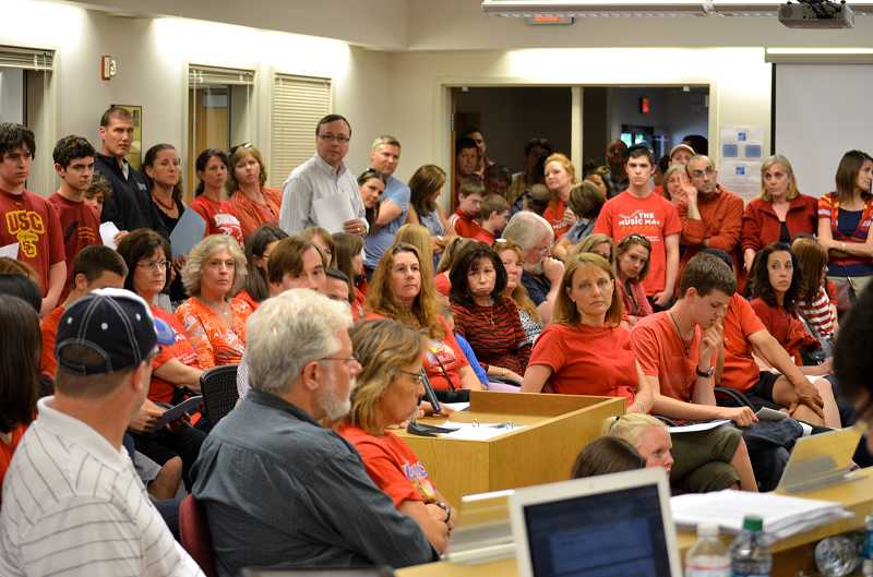 by: TIMES PHOTO: GEOFF PURSINGER - Parents, students and teachers crowded the small meeting room, spilling out into the hallways and sitting on the floor to find room. The district announced Monday that the choir programs would be spared, thanks to a promise made by Washington County and the city of Hillsboro