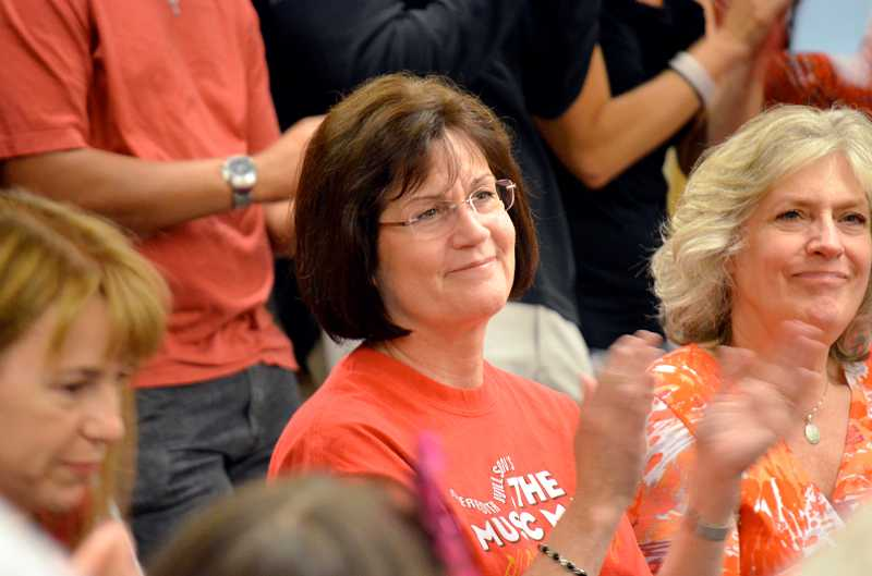 by: TIMES PHOTO: GEOFF PURSINGER - Twality Middle School drama teacher Kathy Thielen applauds after the distrcit announces that choir programs at her school will be saved. Under a plan by the district, she would have been forced to teach choir next year after the schools choir director was transfered to another school.
