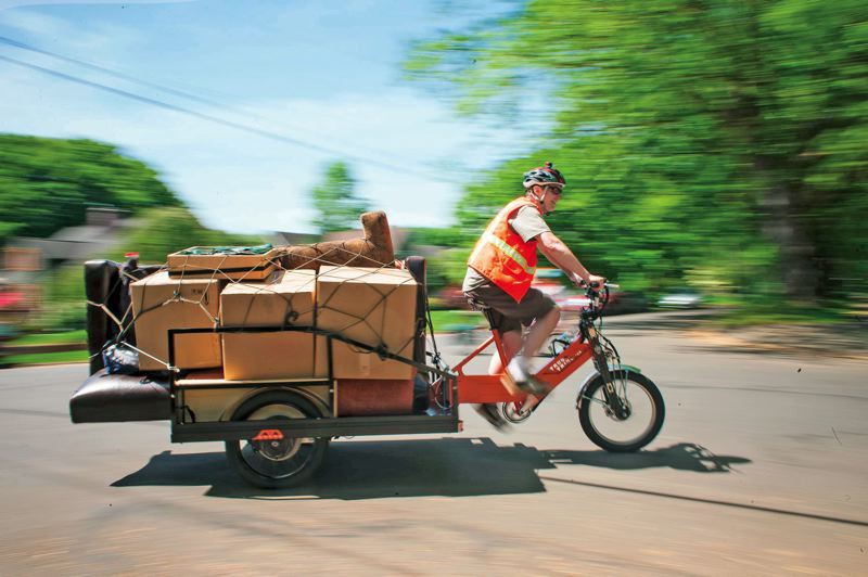 by: PAMPLIN MEDIA GROUP: CHRISTOPHER ONSTOTT - Loaded with furniture, Bill Stites rides his Truck Trike, a bike that he designed and built, five miles across town during a recent move-by-bike event.