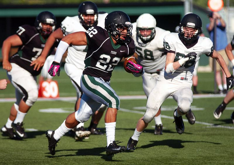 by: DAN BROOD - A.J. ON THE GO -- Black team fullback A.J. Hotchkins looks for running room during Saturday's Tigard Chicken and Bean Bowl. The Black squad scored a 60-54 win over the White team.