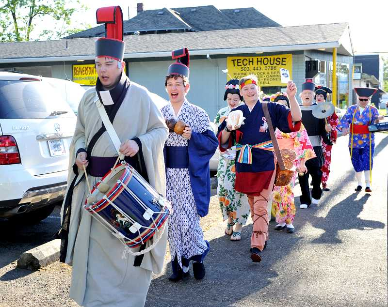 by: TIMES PHOTOS: JOHN LARIVIERE - Members of The Dairyville Players stroll down First Street singing chants from their current production of 'The Mikado,' opening June 21 in the Alpenrose Opera House.