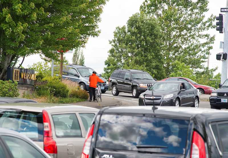 by: TIMES PHOTO: CHASE ALLGOOD - A lone bicyclist struggles to find a safe way over the 185th Avenue bridge across Sunset Highway, despite sidewalks and bike lanes on it.