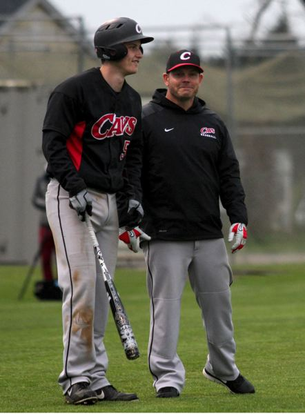 by: JONATHAN HOUSE - Austin Kelly (left) and Clackamas coach John Arntson discuss hitting strategies during a Three Rivers League game with Oregon City. Kelly has been honored as the 2013 Oregon Class 6A high school baseball Pitcher of the Year and Arntson has been honored, along with Sheldon coach Stan Manley, as 6A baseball Coach of the Year.